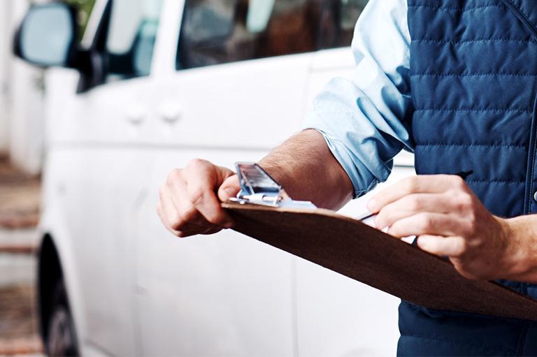Mężczyzna wypełnia dokumenty przy samochodzie